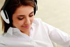 Musica d'ascolto della giovane bella donna di affari in cuffie Fotografia Stock