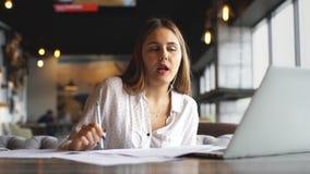 Musica d'ascolto della giovane bella donna di affari in cuffie al caffè e lavorare al computer portatile video d archivio