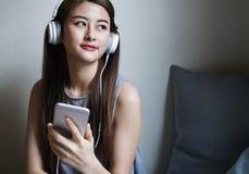 Musica d'ascolto della giovane donna asiatica Immagine Stock Libera da Diritti