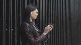 Musica d'ascolto della giovane donna attraente sullo smartphone nella città archivi video