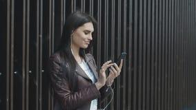 Musica d'ascolto della giovane donna attraente sullo smartphone nella città stock footage