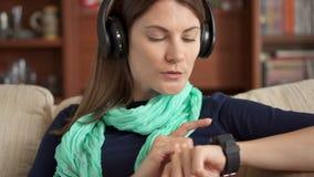 Musica d'ascolto della giovane donna a casa con le cuffie senza cordone senza fili e canto, schermo di spillatura dell'orologio a archivi video