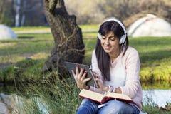 Musica d'ascolto della giovane donna con la sua compressa in un parco di autunno Fotografia Stock