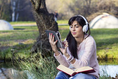 Musica d'ascolto della giovane donna con la sua compressa in un parco di autunno Fotografie Stock Libere da Diritti