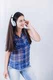 Musica d'ascolto della giovane donna con le cuffie Fotografia Stock