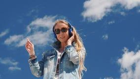 musica d'ascolto della giovane donna con le cuffie all'aperto archivi video