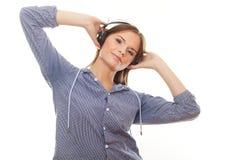 Musica d'ascolto della giovane donna in cuffie fotografia stock libera da diritti