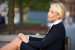 Musica d'ascolto della giovane donna di affari Immagini Stock Libere da Diritti