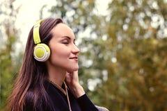 Musica d'ascolto della giovane donna felice dallo smartphone con le cuffie in un parco calmo fotografia stock