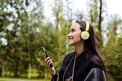 Musica d'ascolto della giovane donna felice dallo smartphone con le cuffie in un parco calmo Immagine Stock Libera da Diritti