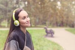 Musica d'ascolto della giovane donna felice dallo smartphone con le cuffie in un parco calmo Fotografia Stock Libera da Diritti