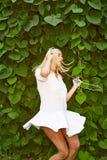 Musica d'ascolto della ragazza con le cuffie e ballare sul fondo della natura Fotografie Stock