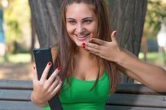 Musica d'ascolto della ragazza con le cuffie e la tenuta dello smartphone Immagine Stock