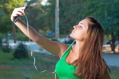 Musica d'ascolto della ragazza con le cuffie e la tenuta dello smartphone Fotografie Stock