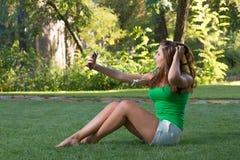 Musica d'ascolto della ragazza con le cuffie e la tenuta dello smartphone Immagini Stock