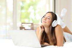 Musica d'ascolto della ragazza con le cuffie ed il computer portatile Fotografie Stock