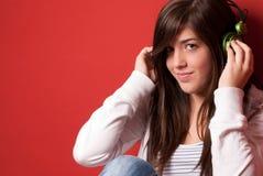 Musica d'ascolto della ragazza con le cuffie su colore rosso Fotografia Stock