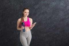 Musica d'ascolto della ragazza felice di forma fisica sullo smartphone e sull'acqua potabile immagini stock libere da diritti
