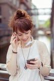 Musica d'ascolto della ragazza sul suo telefono facendo uso della cuffia Fotografia Stock Libera da Diritti