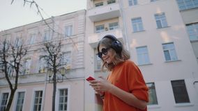 Musica d'ascolto della ragazza sveglia in cuffie, nello stile urbano, anni dell'adolescenza alla moda dei pantaloni a vita bassa  stock footage