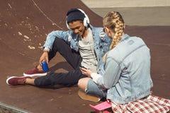 Musica d'ascolto delle coppie dei pantaloni a vita bassa con le cuffie e siiting nel parco del pattino Fotografia Stock Libera da Diritti