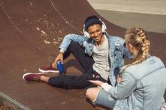 Musica d'ascolto delle coppie dei pantaloni a vita bassa con le cuffie e siiting nel parco del pattino Fotografia Stock