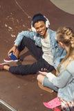 Musica d'ascolto delle coppie dei pantaloni a vita bassa con le cuffie e siiting nel parco del pattino Fotografie Stock