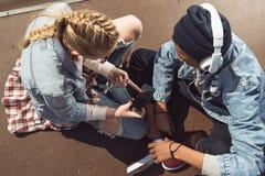 Musica d'ascolto delle coppie dei pantaloni a vita bassa con le cuffie e siiting nel parco del pattino Immagine Stock Libera da Diritti