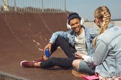 Musica d'ascolto delle coppie dei pantaloni a vita bassa con le cuffie e siiting nel parco del pattino Immagini Stock Libere da Diritti