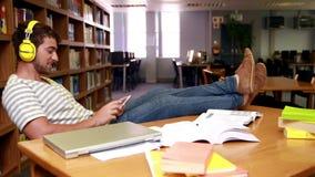 Musica d'ascolto dello studente felice con il piede sulla tavola archivi video