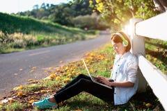 Musica d'ascolto di rilassamento delle giovani donne con il taccuino che si siede sull'erba Fotografia Stock
