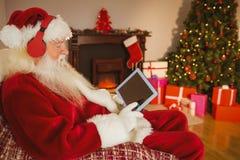 Musica d'ascolto di Santa e compressa commovente Fotografie Stock