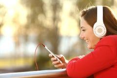Musica d'ascolto di signora dallo Smart Phone Fotografie Stock