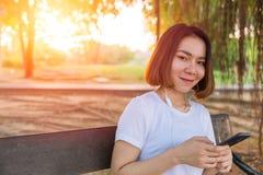 Musica d'ascolto di sorriso teenager asiatico dal suo telefono Fotografia Stock