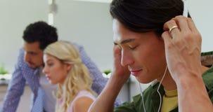 Musica d'ascolto esecutiva felice sulle cuffie allo scrittorio 4k video d archivio