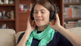 Musica d'ascolto felice allegra della giovane donna a casa con le cuffie senza cordone senza fili ed il canto video d archivio