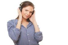 Musica d'ascolto felice della giovane donna in cuffie fotografia stock libera da diritti