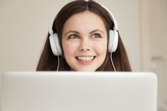 Musica d'ascolto felice della giovane donna in cuffie immagini stock libere da diritti