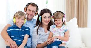 Musica d'ascolto sorridente della famiglia con le cuffie Immagine Stock