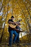 Musica del gioco dei musicisti nella foresta di autunno fotografie stock libere da diritti