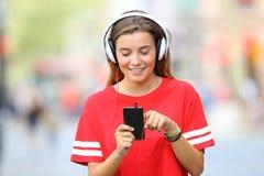 Musica di camminata e d'ascolto teenager sulla via Immagine Stock