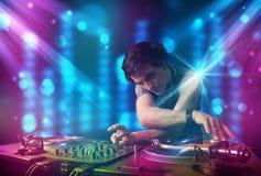 Musica di miscelazione del DJ in un club con le luci blu e porpora Immagine Stock Libera da Diritti