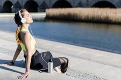 Musica di riposo e d'ascolto della donna in buona salute con il telefono cellulare mentre facendo yoga e allenamento Immagini Stock Libere da Diritti