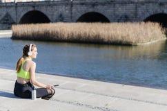 Musica di riposo e d'ascolto della donna in buona salute con il telefono cellulare mentre facendo yoga e allenamento Immagine Stock Libera da Diritti