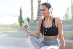 Musica di riposo e d'ascolto della donna di sport facendo uso del suo telefono cellulare in scale Immagini Stock