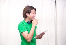 Musica di risata e d'ascolto del ragazzo asiatico facendo uso delle compresse e cuffia Fotografia Stock Libera da Diritti