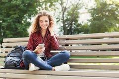Musica di seduta e d'ascolto della bella donna sullo smartphone all'aperto Fotografia Stock