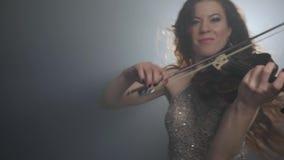 Musica in diretta, bella donna che gioca sullo strumento a corda nell'oscurità nell'illuminazione dei proiettori archivi video