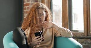 Musica e mandare un sms d'ascolto della ragazza stock footage