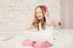 Musica e tecnologia Il ritratto della ragazza in pigiami con il computer portatile bianco e le cuffie rosa senza fili, canta la c Fotografie Stock